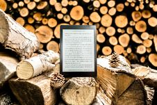 Free Black E-book Reader On Brown Tree Logs Stock Photos - 128558223