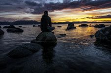 Free Person Sitting On Rock On Body Of Water Royalty Free Stock Photos - 128687418