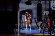 Free Woman Wearing Monokini While Holding Dumbbell Standing Near Black Heavy Bag Stock Images - 128687594