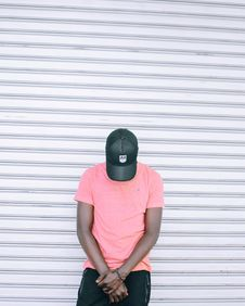 Free Man Wearing Pink Tee Shirt Leaning On Wall While Head Down Royalty Free Stock Photos - 128807928