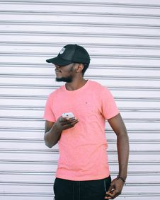 Free Man Wearing Pink T Shirt Holding Smartphone Standing Beside Grey Roll-up Door Stock Image - 128807931