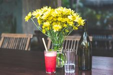Free Yellow Daises In Clear Glass Vase Beside Bottle Stock Photography - 129026622