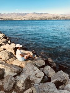 Free Woman Sitting On Rock Near Body Of Water Stock Images - 129026734