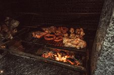 Free Grilled Meat On Black Charcoal Grill At Nighttime Stock Image - 129027341