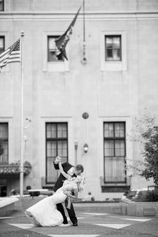 Free Bride And Groom Kissing Near Us Flag Royalty Free Stock Image - 129055786
