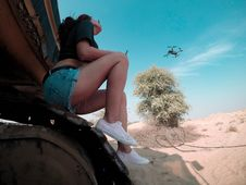 Free Woman Wears Blue Denim Short Shorts And Black Quadcopter Drone Under Clear Blue Sky Royalty Free Stock Images - 129228599