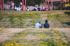Free Two Men Sitting On Yellow Flower Field In The Park Stock Images - 129414594