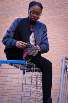 Free Woman Wearing Black Bomber Jacket And Air Jordan 13 Shoes Sitting On Gray Wire Crate Royalty Free Stock Images - 129414999