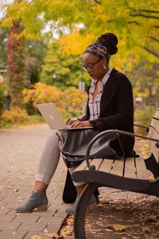 Free Woman Sitting On Brown Outdoor Bench While Using Macbook Royalty Free Stock Photos - 129415028