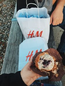 Free Person Holding Muffins Near The Two White H&m S Paper Bags Royalty Free Stock Image - 129501126