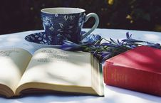 Free Book Opened On Top Of White Table Beside Closed Red Book And Round Blue Foliage Ceramic Cup On Top Of Saucer Stock Image - 129874891
