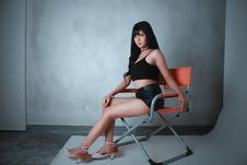 Free Woman Wearing Black Camisole And Short Shorts Sitting On Orange Director S Chair Stock Image - 129874901