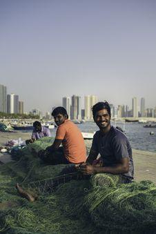 Free Three Men Sitting On Dock Holding Fishing Net Royalty Free Stock Photo - 130178595