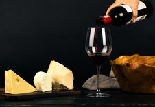 Free Photo Of Person Pouring Wine Into Glass Besides Some Cheese Pairings Stock Photography - 130178672