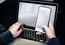 Free Person Using Smartphone While Facing Laptop Computer Royalty Free Stock Image - 130289346