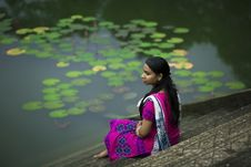 Free Woman In Pink Sari Dress Sitting On Stair Beside Body Of Water Royalty Free Stock Photos - 130289468