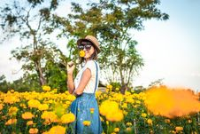 Free Woman Sniffing Yellow Flowers Royalty Free Stock Image - 130290336