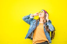 Free Smiling Woman Looking Upright Standing Against Yellow Wall Stock Image - 130492131