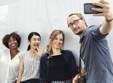 Free Three Smiling Women Beside Man Holding Smartphone Stock Images - 130492314