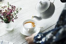 Free Person Holding White Ceramic Teapot And Pouring Tea In Cup Stock Image - 130492371