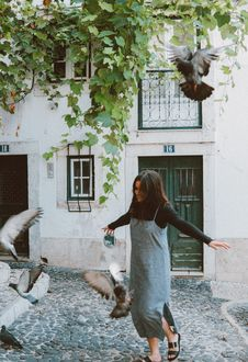 Free Woman Chasing Flock Of Pigeons Stock Image - 130492471