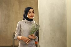 Free Woman In Gray Sweater Holding Flowers Stock Images - 130575274