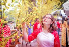 Free Woman Wearing Red And White Raglan-sleeved Shirt Holding Branch Of Yellow Flowering Tree Stock Photos - 130575343