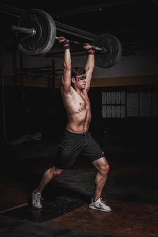 Free Man Lifting A Barbell Stock Image - 130575441