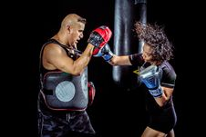 Free Woman Punching The Hand Of Man Wearing Training Gloves Stock Image - 130644731
