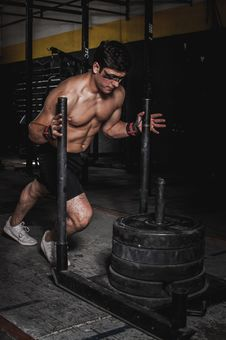 Free Man Pushing Steel Frame With Pile Of Weight Plates Royalty Free Stock Images - 130644859