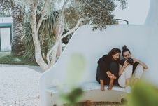 Free Two Women Sitting On White Bench While Looking At Camera Stock Image - 130644901