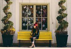 Free Woman Sitting On Yellow Bench Stock Image - 130707081