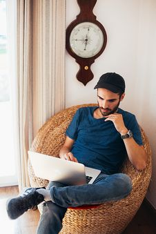 Free Man In Blue Top Sitting On Wicker Chair While Using Laptop Stock Photography - 130896002