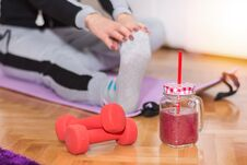 Free Dumbbell And Smoothie In Retro Jar On Floor And Woman Working Stretching Exercises Legs Stock Photos - 130999373