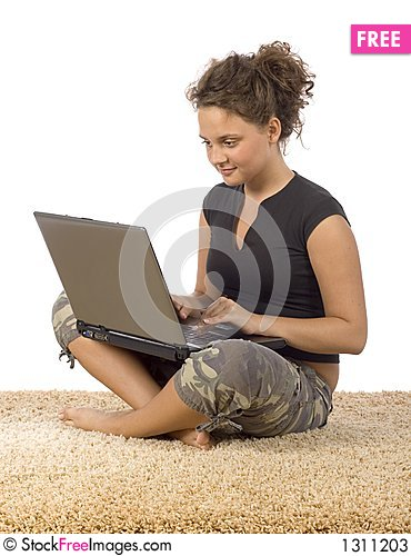 Female teenager sitting on the carpet with laptop Stock Photo