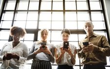 Free Four People Using Smartphones Behind Glass Wall Stock Image - 131017101