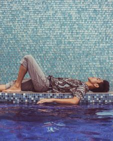 Free Man Lying Down On Pool Side Royalty Free Stock Photography - 131109027