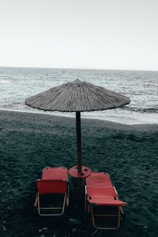 Free Two Red Pool Chairs Under Patio Umbrella Near Shore Royalty Free Stock Photos - 131109038