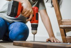 Free Person Using Red And Black Cordless Power Drill On Brown Wooden Bar Stock Image - 131109111