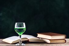 Free Absinthe Drink In Glass And Books With Candle In Candlestick Royalty Free Stock Photo - 131191335