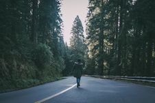 Free Woman Wearing Black Parka Jacket Walking On Black Concrete Road Surrounded By Trees Stock Photo - 131201190
