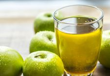 Free Apple Juice In Drinking Glass Beside Green Apples Stock Photography - 131201252