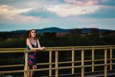 Free Woman Leaning On Yellow Steel Fence On Bridge Stock Images - 131266404