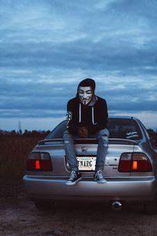 Free Man Wearing Guy Fawkes Mask Sitting On Gray Honda Vehicle Stock Photo - 131266520