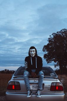 Free Man Wearing Guy Fawkes Mask While Sitting On Silver Honda Civic Stock Photography - 131330202