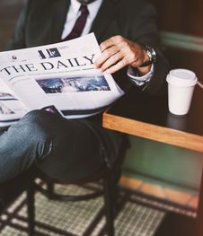 Free Person Sitting On Stool While Reading The Daily Newspaper Stock Photos - 131422963