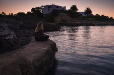 Free Woman Sitting On Edge Of Rock Near Body Of Water Stock Photo - 131613190