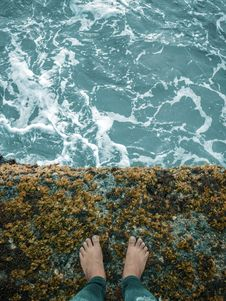 Free Person Standing On Cliff Overlooking Body Of Water Stock Images - 131613644