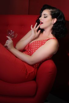 Free Woman In Red Outfit Lying On Red Couch While Holding A Cocktail Glass Royalty Free Stock Images - 131719899