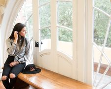 Free Woman Sitting On Brown Bench Beside Closed Door Stock Image - 131720171